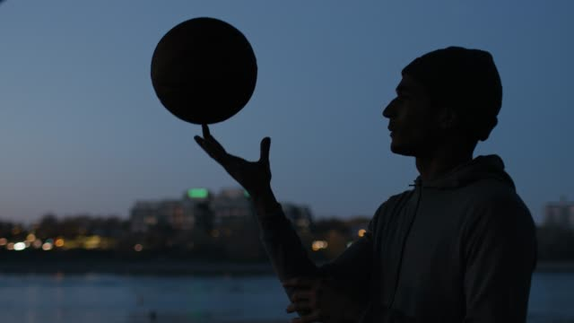 Athlete spinning basketball on finger at night