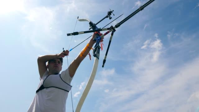 vidéos et rushes de l'athlète enfile un arc tout en pratiquant sur un champ de tir. - tir à l'arc
