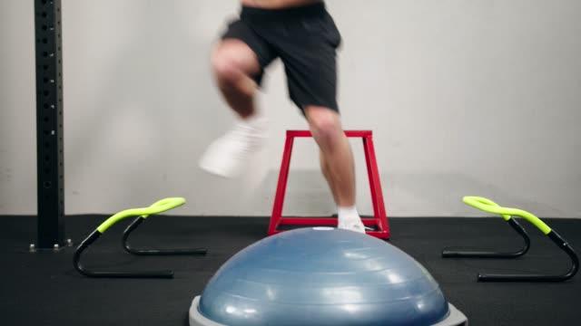 機能性ジムでの障害物とボスボールを持つアスリートウエストダウントレーニング - ボディビル点の映像素材/bロール