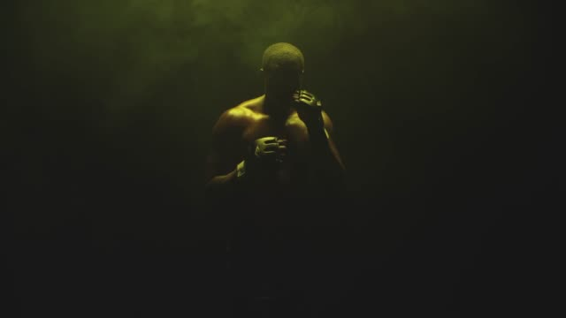 athlete walks forward and shadow boxes on a foggy dark yellow background - box video stock e b–roll