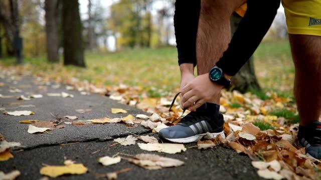 vidéos et rushes de athlète de porter une montre intelligente tout en attachant ses chaussures - chrono sport