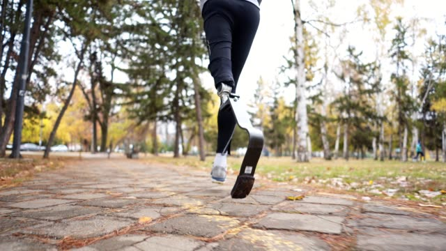 Athlete with a artificial leg running in a city park Young and athletic man with a artificial leg, exercising outdoors, living a healthy lifestyle recovering. artificial limb stock videos & royalty-free footage