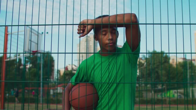 Athlete with basketball leaning on sports fence