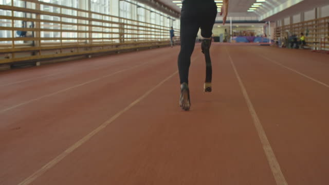 Athlete with Prosthetic Leg on Running Track Following shot with slow motion of amputee athlete with prosthetic leg training on running track at indoor stadium artificial limb stock videos & royalty-free footage