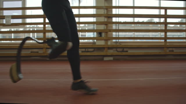 Athlete with Prosthetic Leg Training Low section tracking of amputee sportsman with prosthetic leg training on running track in slow motion at indoor stadium artificial limb stock videos & royalty-free footage