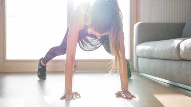 Athlete woman doing plank jumping jack exercise on living room floor