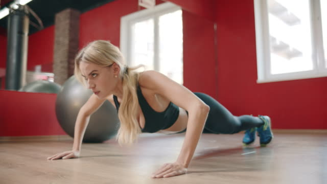 athlete woman training push up exercise in gym club. - autorità video stock e b–roll