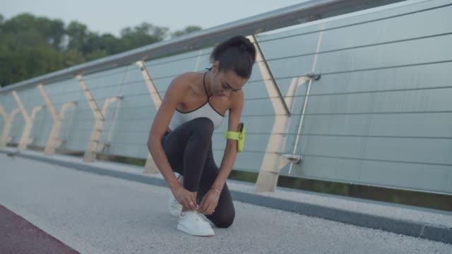 vidéos et rushes de femme d'athlète attachant des chaussures de course pendant le jogging à l'aube - joggeuse