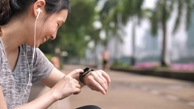 athlete woman using smart watch and listening music - computer indossabile video stock e b–roll