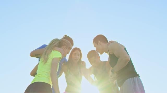 Athleten, die beim Sonnenuntergang gegen klaren Himmel huddeln – Video