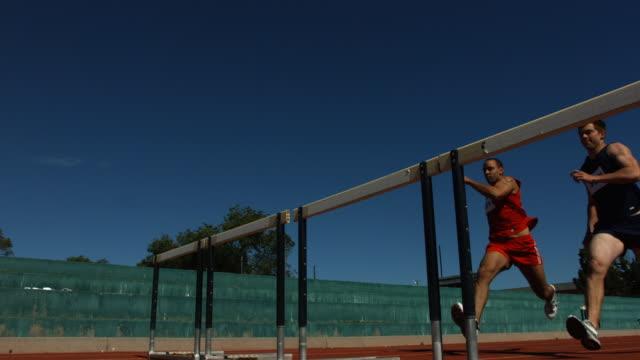 vídeos y material grabado en eventos de stock de atletas jump over obstáculos, cámara lenta - valla artículos deportivos