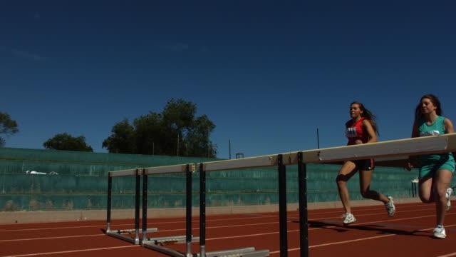 Athletes jump over hurdles, slow motion video
