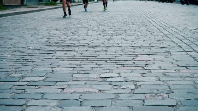 idrottare löper längs vägen asfalterad sten, city marathon, löpares ben närbild, sport konkurrens - tävlingsdistans bildbanksvideor och videomaterial från bakom kulisserna