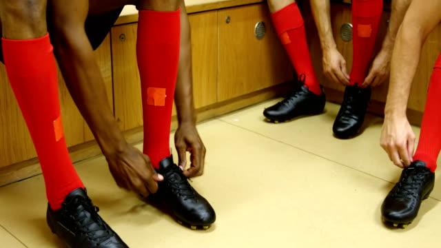 Athletes tying shoe lace in the locker room 4k Three athletes tying shoe lace in the locker room 4k locker stock videos & royalty-free footage