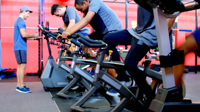 Athletes working out on exercise bike 4k Athletes working out on exercise bike in the gym 4k exercise bike stock videos & royalty-free footage