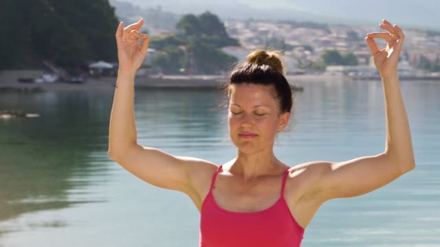 Athletic adult woman practicing mudra yoga at seaside