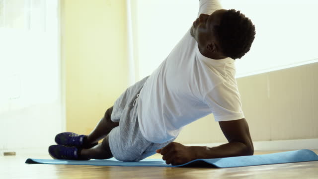 Athletic African American man balancing on one arm while doing side plank exercise on mat in gym