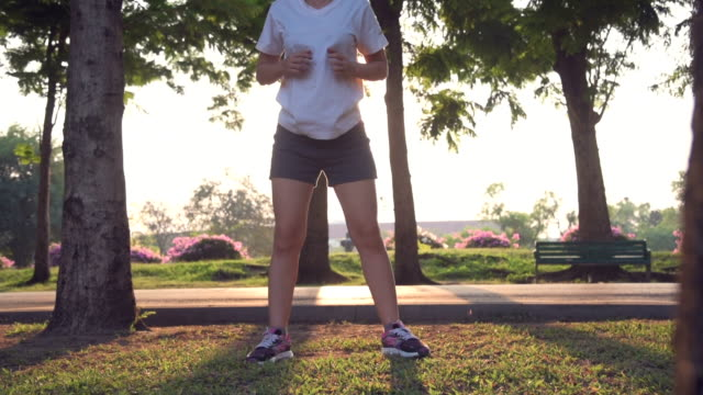 Athletic Asian Woman Stretching In Public Park Athletic Asian Woman Stretching In Public Park, Bangkok, Thailand, Handheld Shot, HD Format only young women stock videos & royalty-free footage