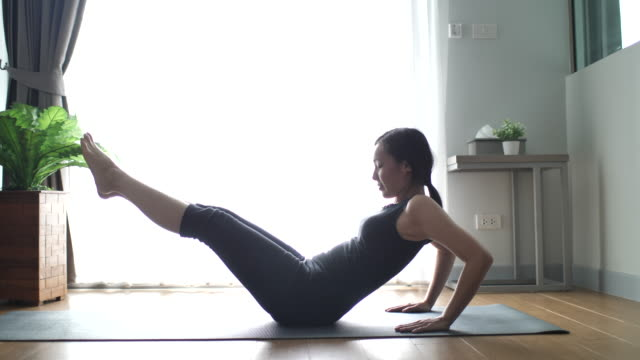 athletic asian young woman doing abdominal crunches while working out at home - irriducibilità video stock e b–roll