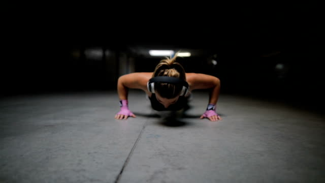 athletic beautiful woman does push-ups - irriducibilità video stock e b–roll