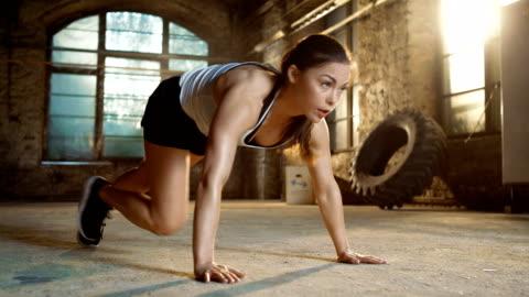 athletic beautiful woman fa running plank come parte della sua routine di allenamento in palestra di cross fitness e bodybuilding. - allenamento video stock e b–roll