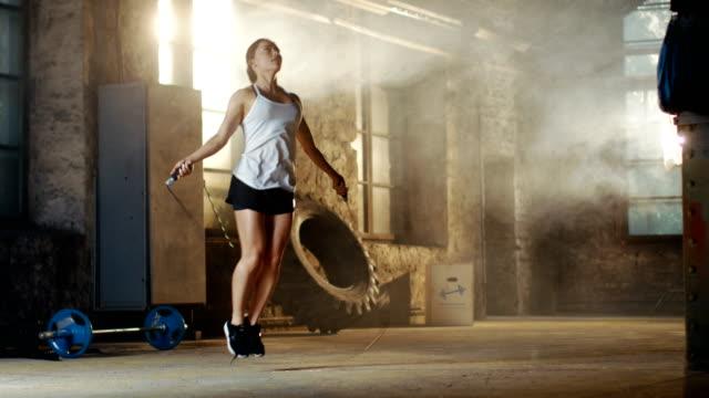 vídeos y material grabado en eventos de stock de hermosa mujer atlética ejercicios con salto / saltar cuerda en un gimnasio. ella hace parte de su entrenamiento físico intenso. - entrenamiento con pesas