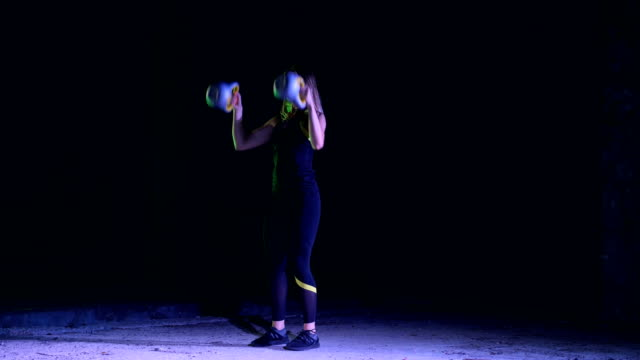 Athletic, beautiful, young woman doing various strength exercises with weights. At night, in light of multi-colored searchlights, in light smoke, fog, in an old abandoned hangar Athletic, beautiful, young woman doing various strength exercises with weights. At night, in the light of searchlights, in light smoke, fog, in an old abandoned building human back stock videos & royalty-free footage