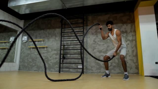 Deportiva hombre negro haciendo batalla cuerdas ejercicio en un club de salud. - vídeo