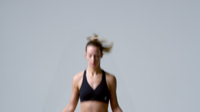 Athletic blonde woman jumping rope, waist up, shot on R3D video