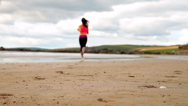 спортивный бег на пляже brunette - спортивный бюстгальтер стоковые видео и кадры b-roll