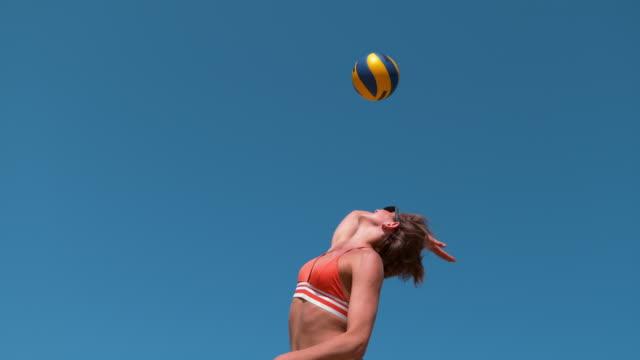 vídeos y material grabado en eventos de stock de cámara lenta: atlético caucásica chica servir la bola durante el juego de voleibol de playa. - juego de vóleibol