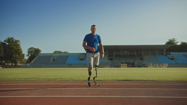 Athletic Disabled Fit Man with Prosthetic Running Blades is Posing During a Training on an Outdoor Stadium on a Sunny Afternoon. Amputee Runner Standing on a Track. Motivational Sports Footage. Athletic Disabled Fit Man with Prosthetic Running Blades is Posing During a Training on an Outdoor Stadium on a Sunny Afternoon. Amputee Runner Standing on a Track. Motivational Sports Footage. prosthetic equipment stock videos & royalty-free footage