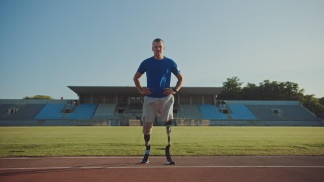 人工ランニングブレードを持つアスレチック障害者フィットマンは、晴れた午後に屋外スタジアムでトレーニング中にポーズをとっています。トラックに立つ切断患者ランナー。モチベーシ� - 四肢点の映像素材/bロール