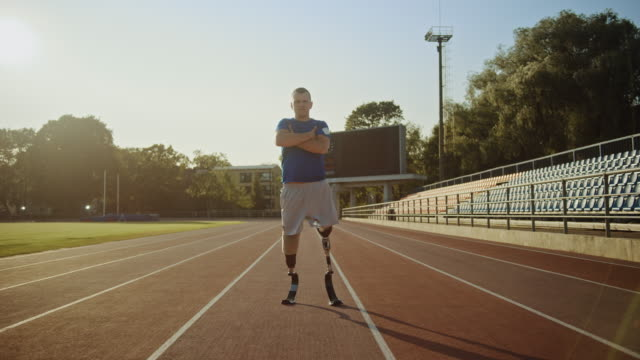 Athletic Disabled Fit Man with Prosthetic Running Blades is Posing with Crossed Arms on an Outdoor Stadium on a Sunny Afternoon. Amputee Runner Standing on a Track. Motivational Sports Footage. Athletic Disabled Fit Man with Prosthetic Running Blades is Posing with Crossed Arms on an Outdoor Stadium on a Sunny Afternoon. Amputee Runner Standing on a Track. Motivational Sports Footage. conquering adversity stock videos & royalty-free footage