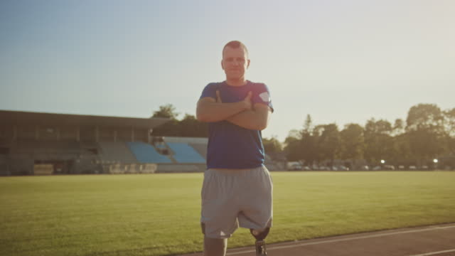 Athletic Disabled Fit Man with Prosthetic Running Blades is Posing with Crossed Arms on an Outdoor Stadium on a Sunny Afternoon. Amputee Runner Standing on a Track. Motivational Sports Footage. Athletic Disabled Fit Man with Prosthetic Running Blades is Posing with Crossed Arms on an Outdoor Stadium on a Sunny Afternoon. Amputee Runner Standing on a Track. Motivational Sports Footage. prosthetic equipment stock videos & royalty-free footage