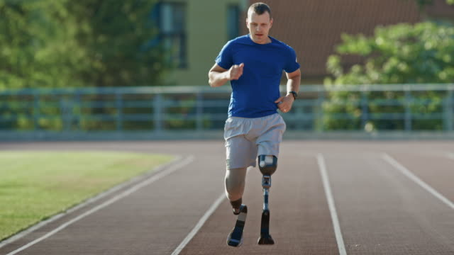 vídeos de stock e filmes b-roll de athletic disabled fit man with prosthetic running blades is training on a outdoors stadium on a sunny afternoon. amputee runner jogging on a stadium track. motivational sports footage. - membro