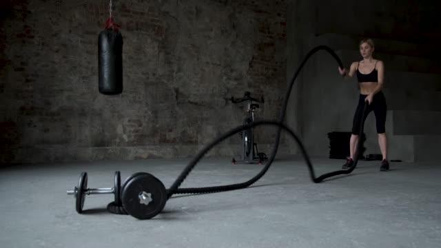 athletische hündin aktiv in einem gym übungen mit kampfseilen während ihres cross fitness workout. zeitlupe - religiöses symbol stock-videos und b-roll-filmmaterial