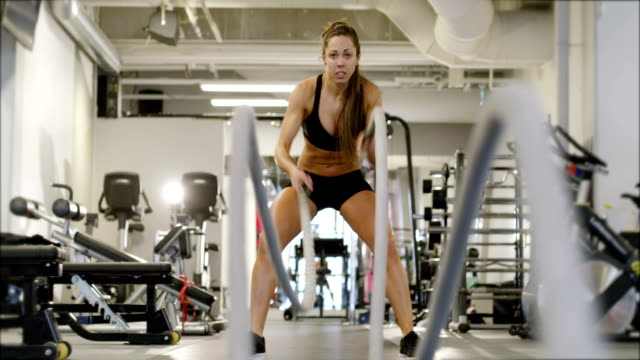 Athletic female high-intensity interval training using battle ropes video