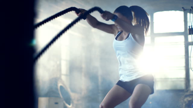 Athletic Female in a Gym Exercises with Battle Ropes During Her Cross Fitness Workout/ High-Intensity Interval Training. She's Muscular and Sweaty, Gym is in Industrial Building. video