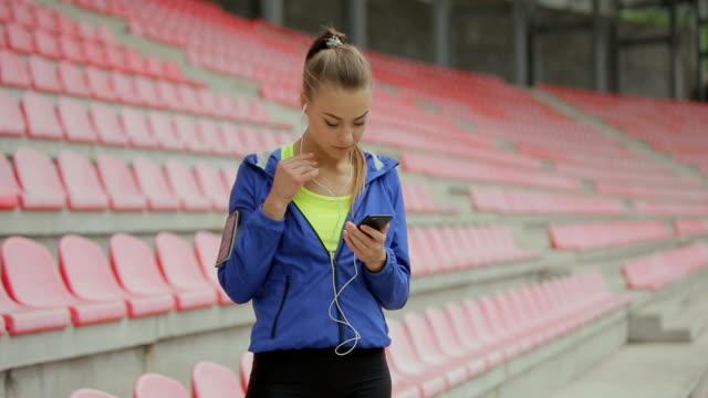 athletic fitness kvinnan ta en paus och använda smartphone på stadion - sportaktivitet bildbanksvideor och videomaterial från bakom kulisserna