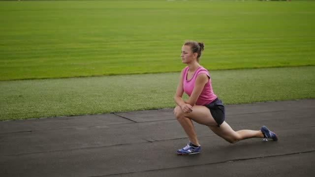 Athletic girl doing lunges limbering up at stadium