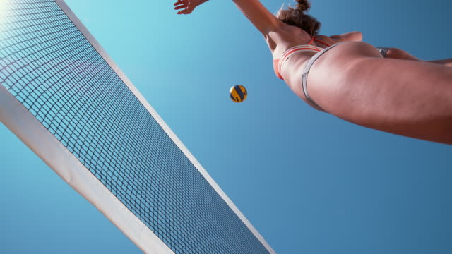 SLOW MOTION: Athletic girl jumps in the air and strikes the ball over the net. SLOW MOTION, BOTTOM UP, CLOSE UP: Athletic Caucasian girl playing beach volleyball jumps in the air and strikes the ball over the net. Sporty young woman playing volleyball on a sunny summer day. volleyball sport stock videos & royalty-free footage