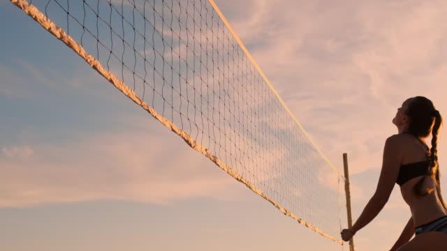 スローモーション、ローアングル、クローズアップ、サンフレア:ビーチバレーをプレイするアスレチックガールは、空気中にジャンプし、美しい夏の夜にネット上でボールを打ちます。白人 - 尖っている点の映像素材/bロール