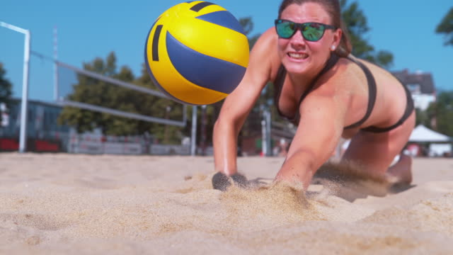 CLOSE UP: Athletic girl playing volleyball dives into the sand to reach the ball SLOW MOTION, CLOSE UP, DOF: Athletic Caucasian girl playing volleyball dives into the sand to reach and strike the ball with one hand. Female athlete saves a point during a beach volleyball game. beach volleyball stock videos & royalty-free footage