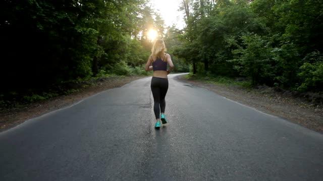 atletisk flicka kör på vägen i skogen. utomhus fitness. sköt med steadicam - tävlingsdistans bildbanksvideor och videomaterial från bakom kulisserna