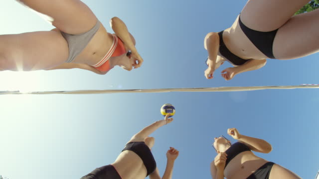 SLOW MOTION: Athletic girls having fun playing beach volleyball on a sunny day. SLOW MOTION, BOTTOM UP, LENS FLARE: Athletic Caucasian girls having fun playing beach volleyball on a sunny day. Four fit Caucasian women passing the ball over the volleyball net in the hot summer sun beach volleyball stock videos & royalty-free footage