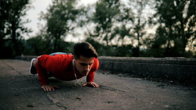 athletic man doing push-up on a road at sunset. - man city exercise abs video stock e b–roll