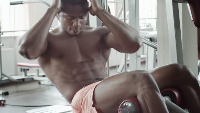 sportlicher mann ausführen bauchmuskelübungen - männliches tier stock-videos und b-roll-filmmaterial