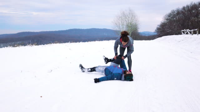 vídeos de stock e filmes b-roll de athletic man experiencing sports injury while running on a snow with his girlfriend. - cair