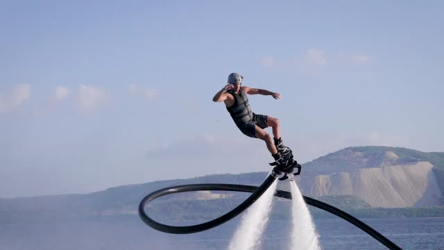 athletic man flying with jet pack in sly - adrenalina video stock e b–roll
